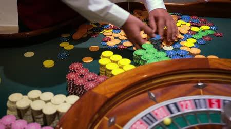 соблазнять : table game in a casino with the roulette in a casino and the dealers hand the dealer chips. Full HD