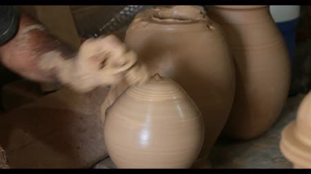 louça de barro : Hands of a man close-up, creating cans or vases of gray clay. Mans hands make a clay pitcher. Potter makes a pitcher. UltraHD