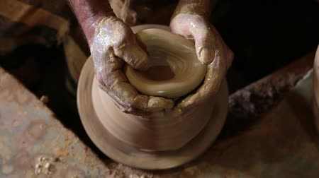 louça de barro : Potter works with clay. Hands of a man close-up, creating cans or vases of clay. Mans hands make a clay pitcher. Potter makes a pitcher. FullHD