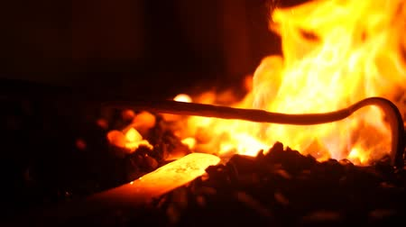 forging sword : Pilling Coals in a Burning Fire in a Blacksmith Forge Stock Footage