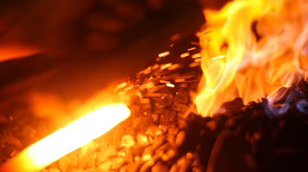 heating up metal : Blacksmith Forging a Sword in His Workshop with Sparks and Fire