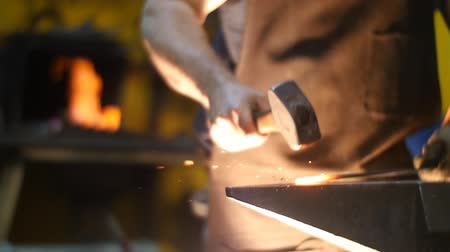 heating up metal : Blacksmith Forging a Sword with Hammer on an Anvilin a Workshop Slow Motion Stock Footage