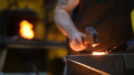 forging sword : Blacksmith Hammering Hot Metal on an Anvil with Sparks in a Workshop Stock Footage