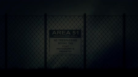 район : Zoom in into an Area 51 Sign on a Metal Fence on a Stormy Night