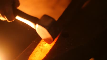 forging sword : A Blacksmith Forging a Sword with a Hammer on an Anvil in Slow Motion