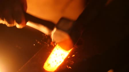 forging sword : A Blacksmith Banging Hot Metal with a Hammer on an Anvil