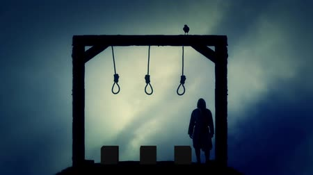 until : Executioner Standing in the Gallows in a Dark Cloudy Day