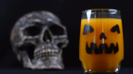 маска : Halloween. A glass of juice and skull behind.