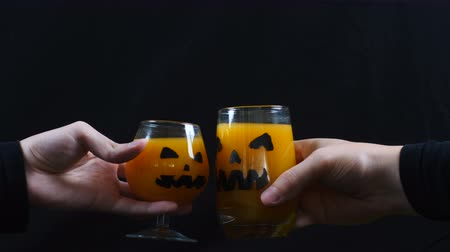 самодельный : Halloween. linking glasses of juice. Black background.