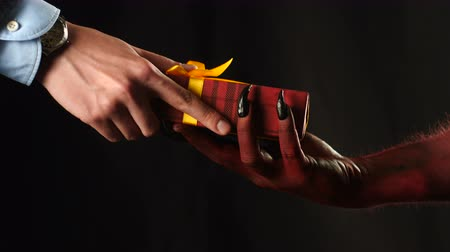 подарок : Red demon hand gives a gift to the businessman. Стоковые видеозаписи