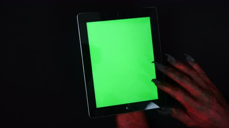 ebook : Devils hand uses tablet PC with a green screen.