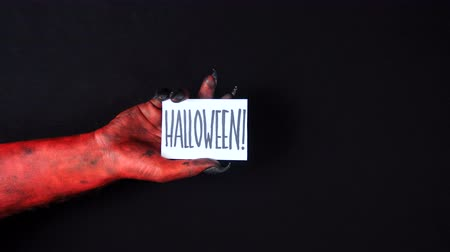 dismay : Red demon hand holding halloween card.