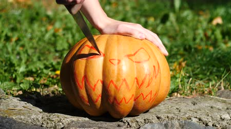 terribly : Halloween. Man carves a face in a pumpkin to make a jack olantern. Stock Footage