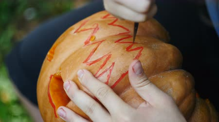 terribly : Halloween. Man carves a mouth in a pumpkin to make a jack olantern. Stock Footage