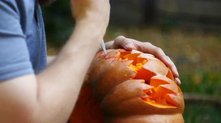terribly : Halloween. Man carves teeth in a pumpkin to make a jack olantern.