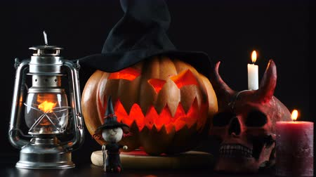 terribly : Halloween. Pumpkin, skull, oil lamp, candle, witch standing on table.