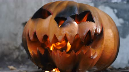 frightful : Halloween. Burning charred pumpkin.