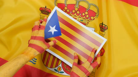feloszt : Catalan hands put the flag of Catalonia on the flag of Spain Stock mozgókép