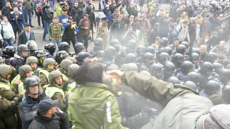 плохо : KYIV, UKRAINE - OCT 17, 2017: Detachment of policemen in helmets move along the street and and use tear gas. Стоковые видеозаписи