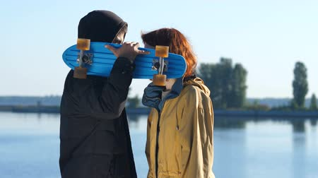 compreensão : Young couple of skaters kissing behind skateboard Vídeos