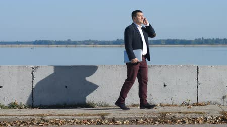 dávat : a man in a suit speaks on the phone beside the river