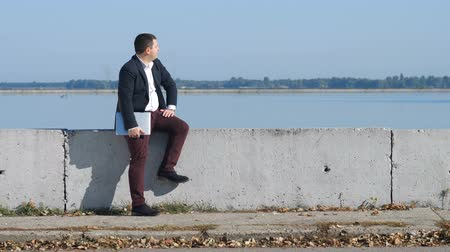 легкий : Businessman in suit sits by the river and looks at time
