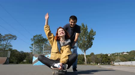 compreensão : The guy rolls the girl on a skateboard