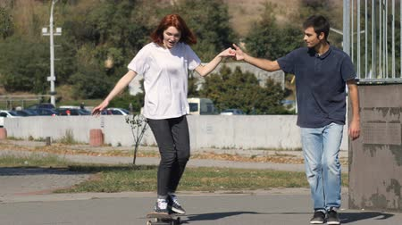 понимание : Guy teaches a girl how to ride a skateboard