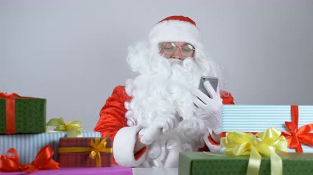 nativo : Santa Claus uses a mobile phone and laughs 50 fps Stock Footage