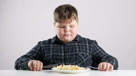 unconditional : Young fat boy prepared to eat salad 50 fps Stock Footage
