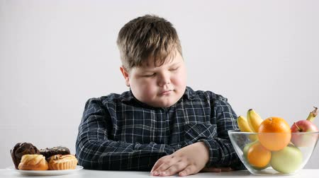 doubt : Young fat boy chooses fruit instead of cakes 50 fps