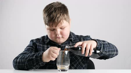 cola : Young fat boy pours soda into a glass 50 fps