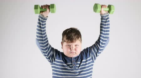 pumping : Young fat boy does the exercise with dumbbells pumps the shoulders 50 fps