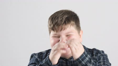vigorous : Young fat boy laughs and closes his eyes with his hands 50 fps Stock Footage