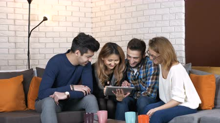 discurso : Multinational company sit on the couch and discuss funny video seen on the tablet 50 fps Vídeos