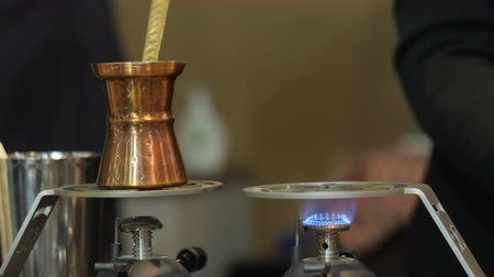 turk : Man lights a burner and puts a Jezve coffee