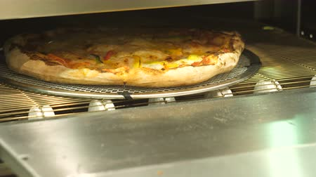 nutricional : Pizza moving out of the automatic oven, cheese melting.