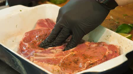 veal recipe : Hands in black gloves pour oil on meat Stock Footage