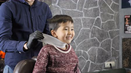professionally : Barber in black gloves is preparing an Asian child for a haircut 60 fps