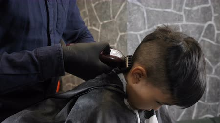 professionally : Barber in black gloves shaves the Asian child back of the head 60 fps Stock Footage