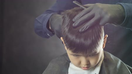 professionally : Barber in black gloves carefully shaves the nape of an Asian child in a barber shop, front view 60 fps