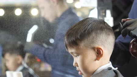professionally : Barber in black gloves spraying and combing hair of a asian child 60 fps Stock Footage