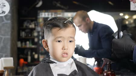 professionally : Barber in black gloves gently shaves bangs Asian boy 60 fps