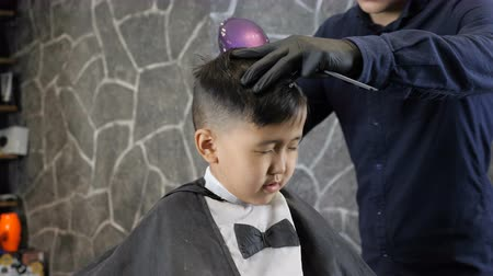 professionally : Barber in black gloves dries Asian boy with hair dryer 60 fps