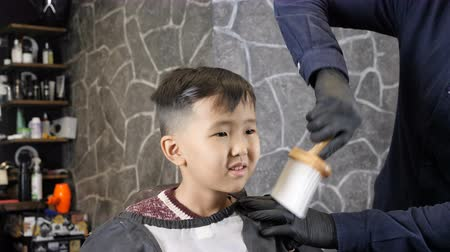 professionally : Barber in black gloves removes hair from the neck of an Asian child 60 fps