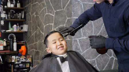 professionally : Barber in black gloves spraying and combing on the hair of an Asian kid 60 fps Stock Footage