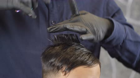professionally : Barber in black gloves cuts hair on the crown of an Asian child, close up 60 fps Stock Footage