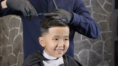 professionally : Barber in black gloves cuts hair on the crown of an Asian child 60 fps