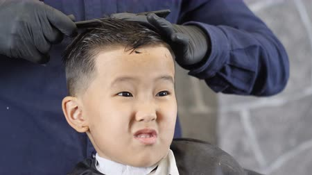 professionally : Barber in black gloves cuts hair on the crown of an Asian child, the boy is in shock 60 fps