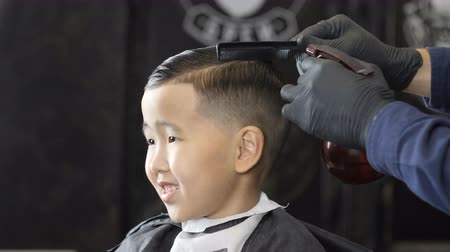 professionally : Barber in black gloves sprinkles water on the hair of an Asian child and combs them 60fps